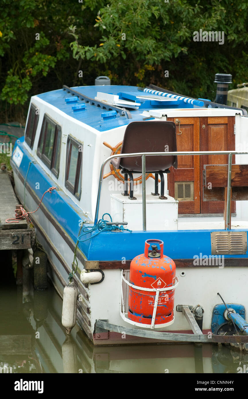 Boat moored in a marina carrying bottles of propane gas. - Stock Image