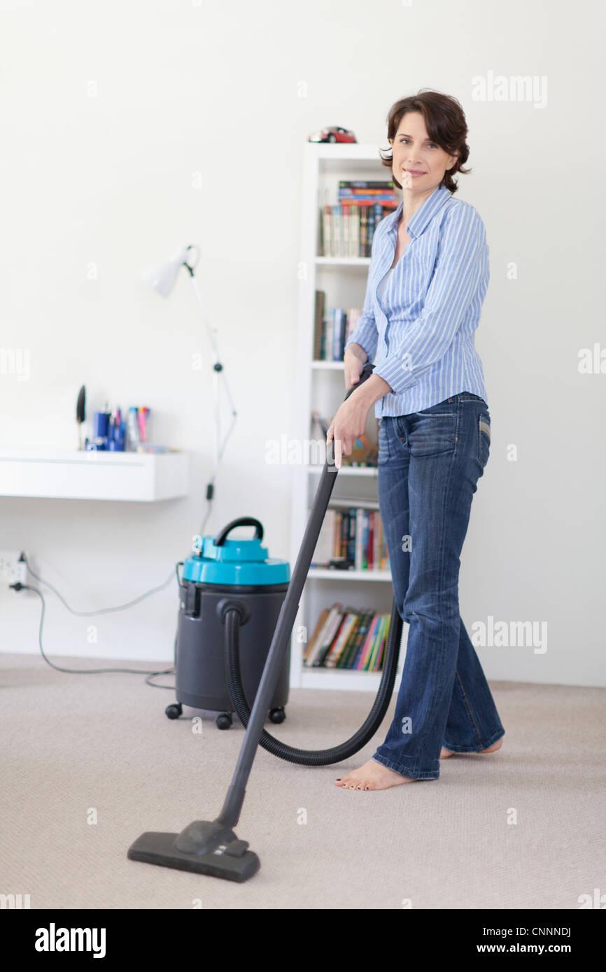 Smiling woman vacuuming living room - Stock Image