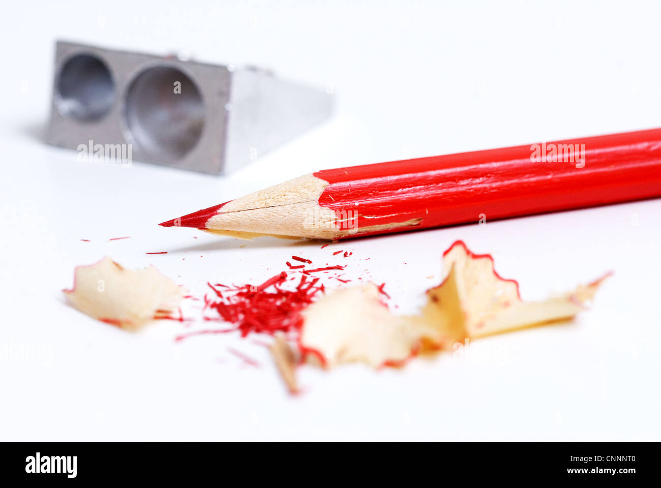 Red coloured pencil and sharpener on white background. - Stock Image