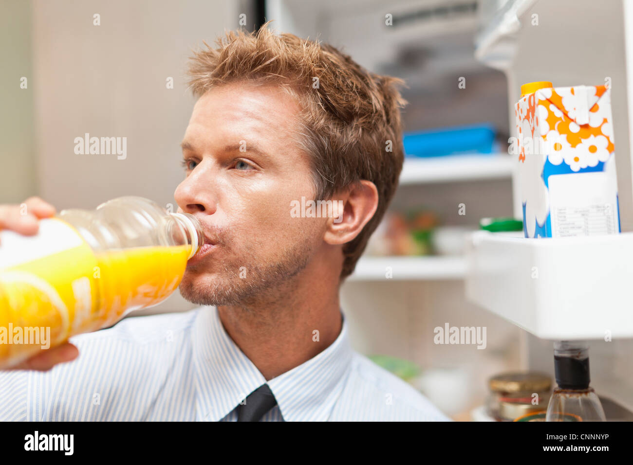 Man drinking juice out of bottle - Stock Image