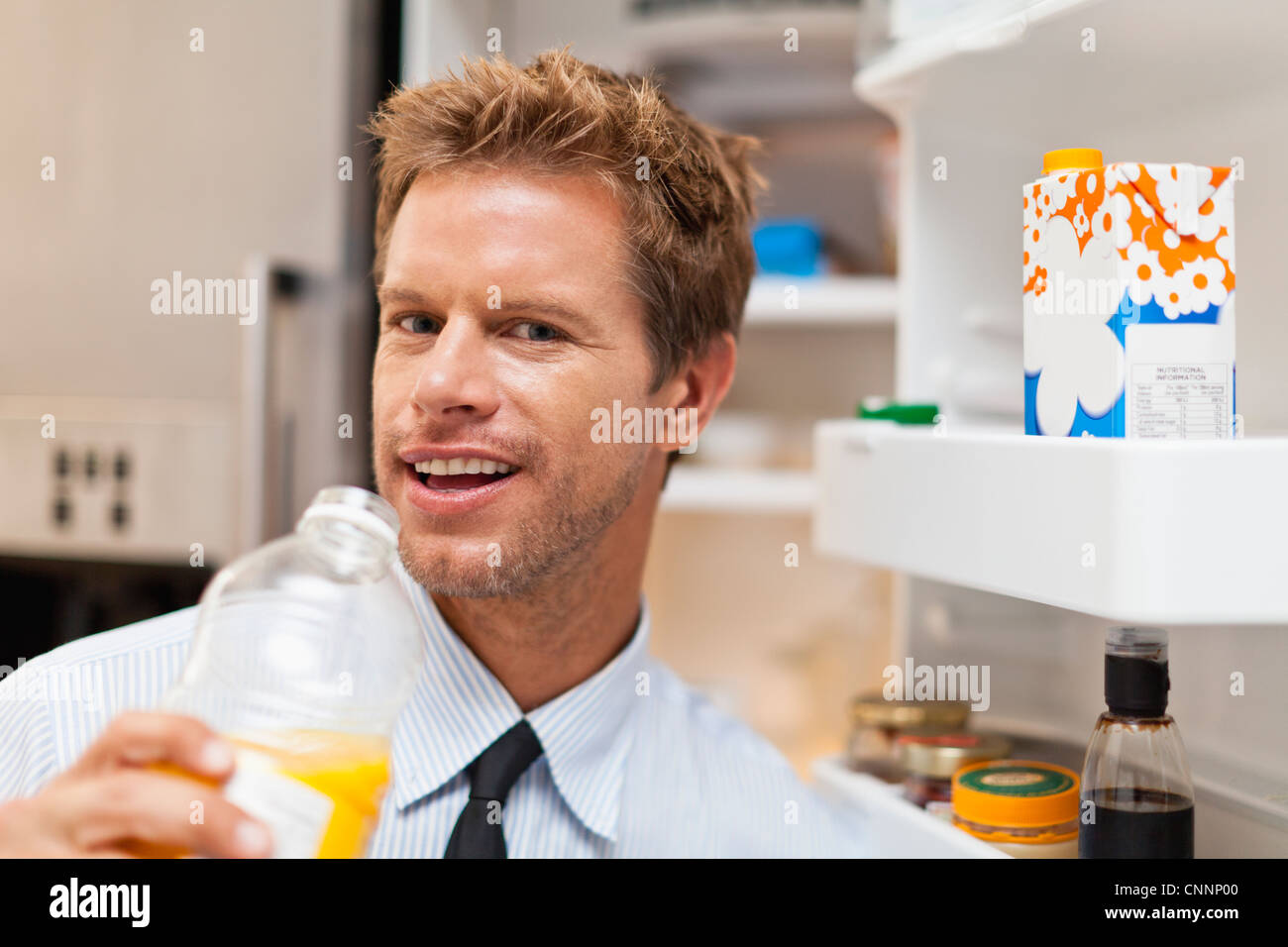 Man drinking juice out of pitcher - Stock Image