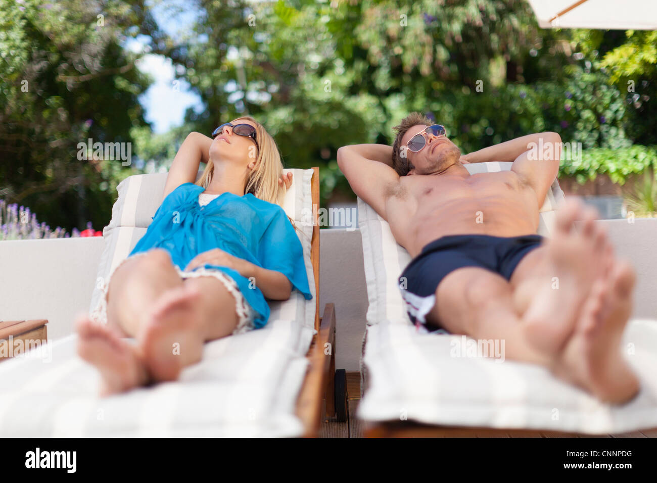 Couple relaxing in lawn chairs - Stock Image