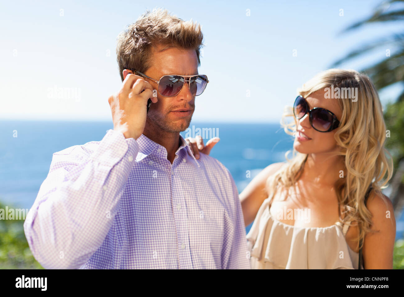 Man ignoring girlfriend for cell phone - Stock Image