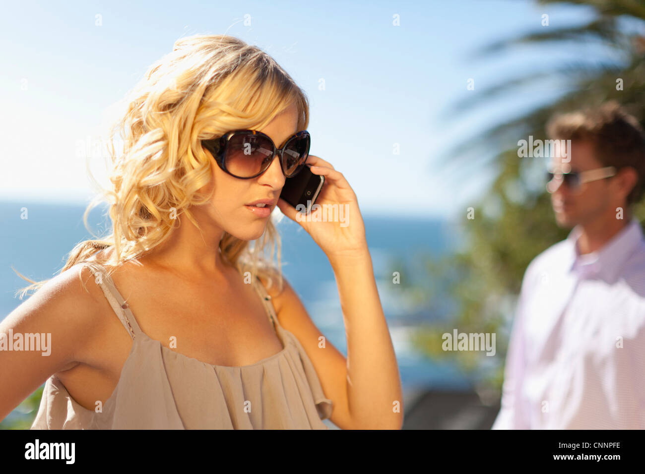 Woman ignoring boyfriend for cell phone - Stock Image