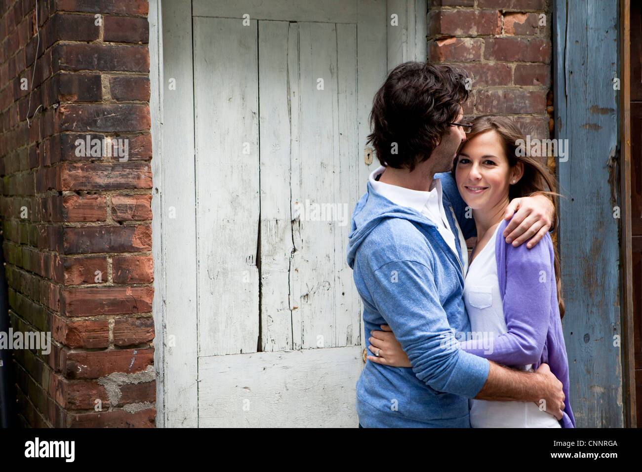 Portrait of Young Couple Embracing in Alleyway Stock Photo