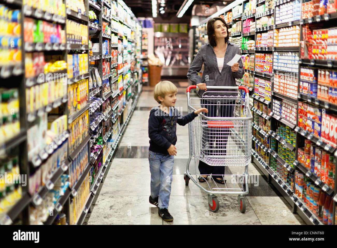 Woman grocery shopping with son - Stock Image