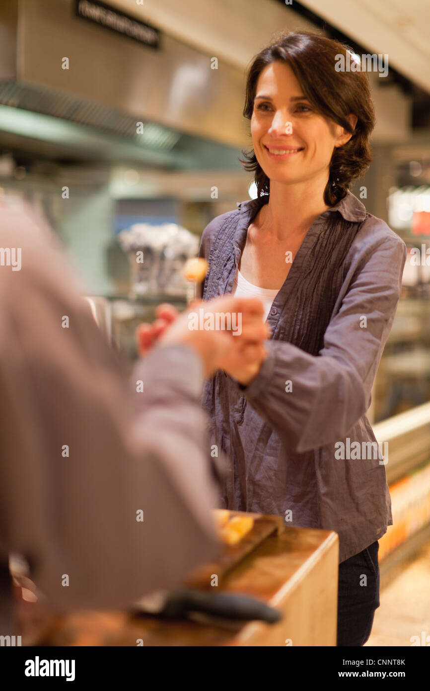 Woman with free samples in grocery store - Stock Image