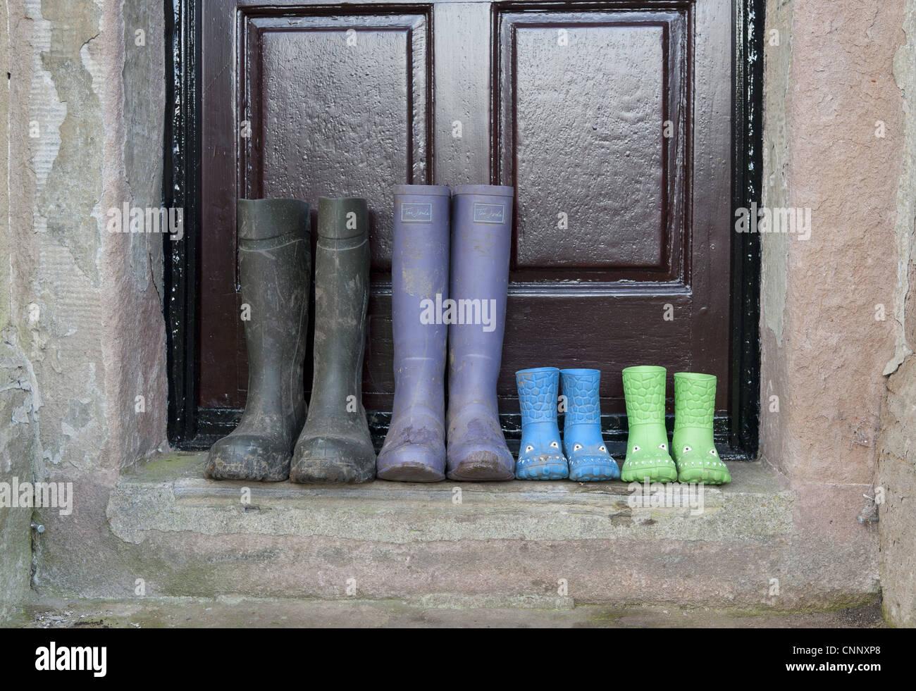 Four pairs wellington boots two children's pairs one women's pair men's pair outside farmhouse door Whitewell Lancashire Stock Photo