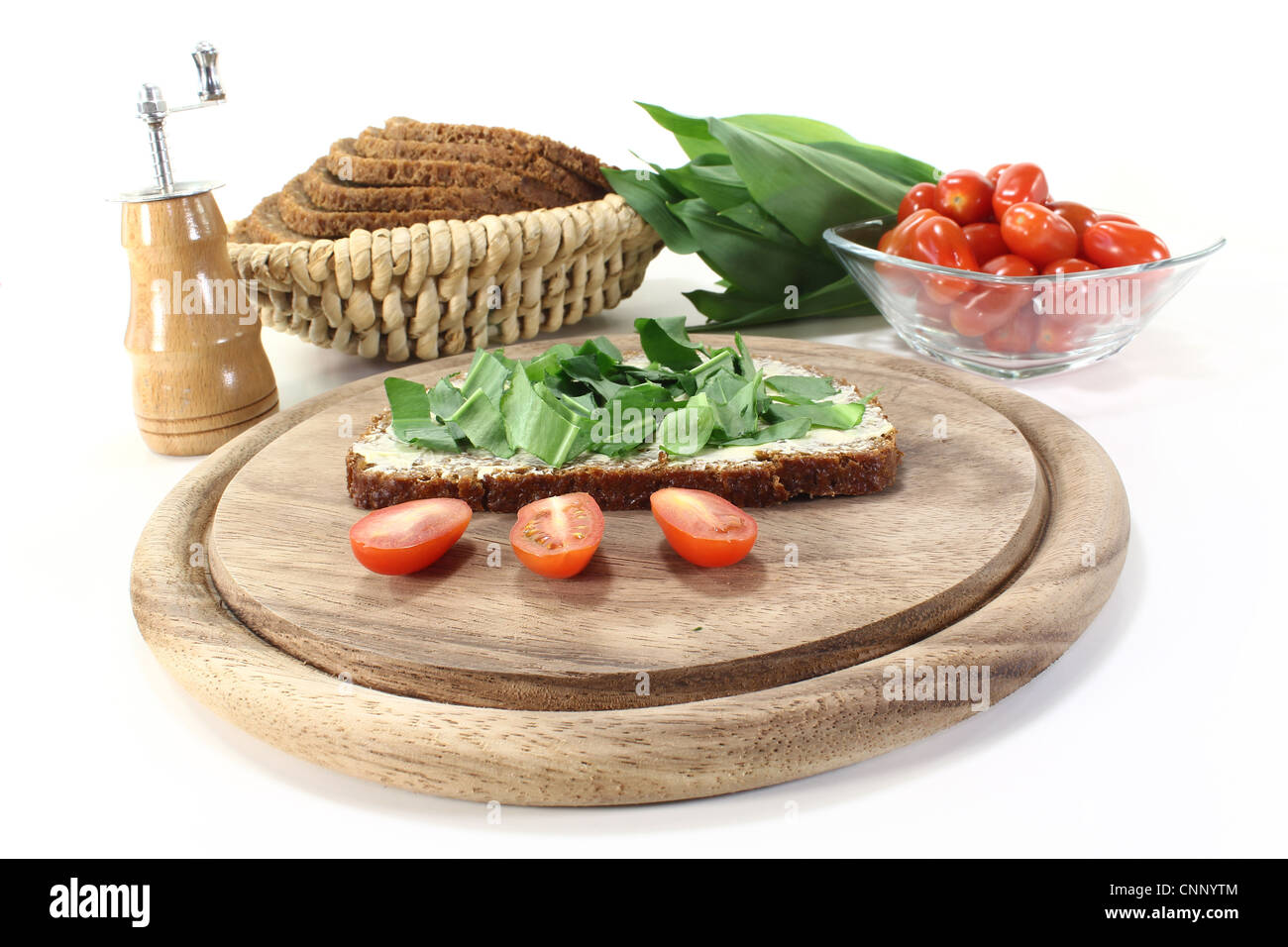 ramson bread with butter, fresh ramson and tomatoes on a light background - Stock Image