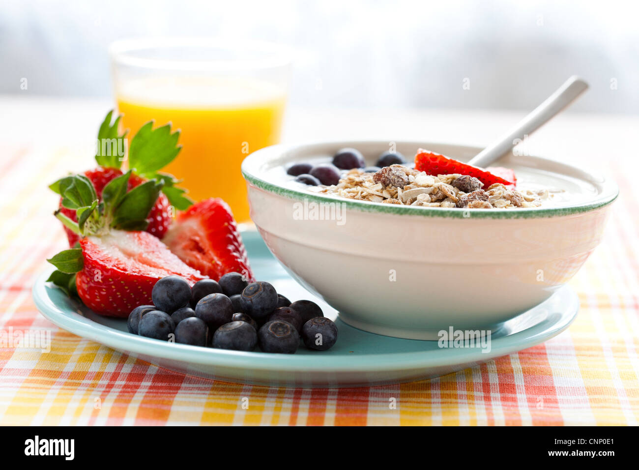 Bowl of muesli with yoghurt, strawberries and blueberries, boiled egg and orange juice for healthy breakfast - Stock Image