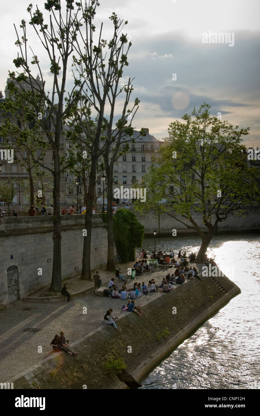 Parisians relaxing on the banks of the Seine, Paris. - Stock Image