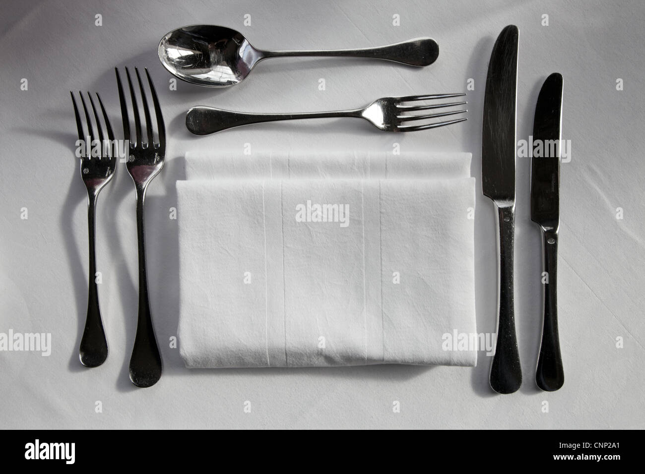 Silver cutlery set out for dinner service. - Stock Image