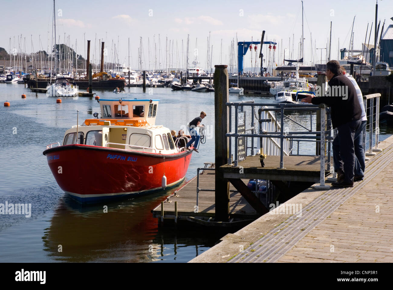 Lymington harbour - boat trip mooring - boy leaping ashore with rope - a decisive moment - passers by watching - Stock Image