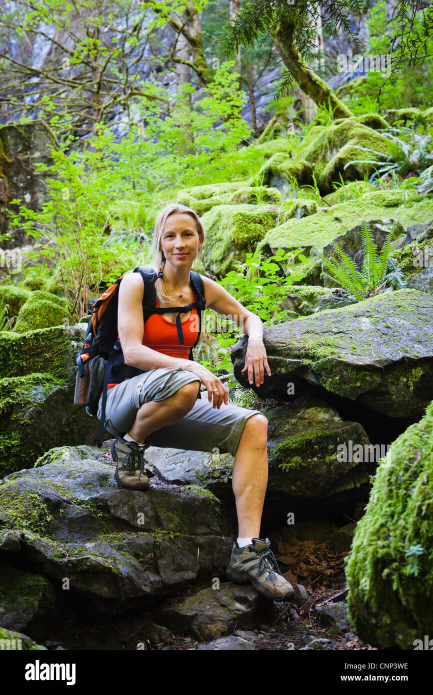 An athletic woman posing for a portrait on a rocky path amongst moss covered rocks, Little Si trail, Washington, - Stock Image
