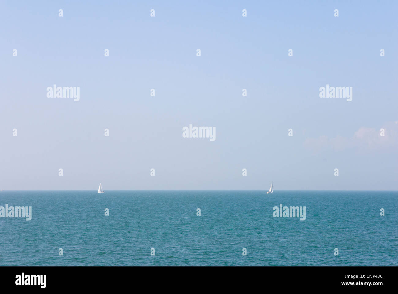 Blue/green sea blue sky white sails on the horizon moving apart - Stock Image