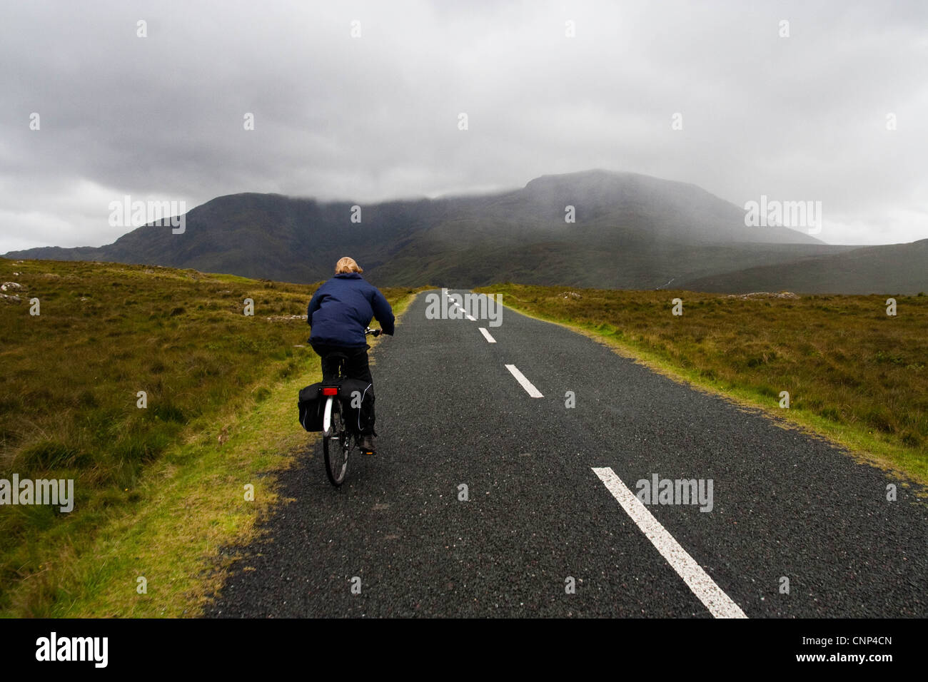 Girl cycling along a country road in the West of Ireland Stock Photo