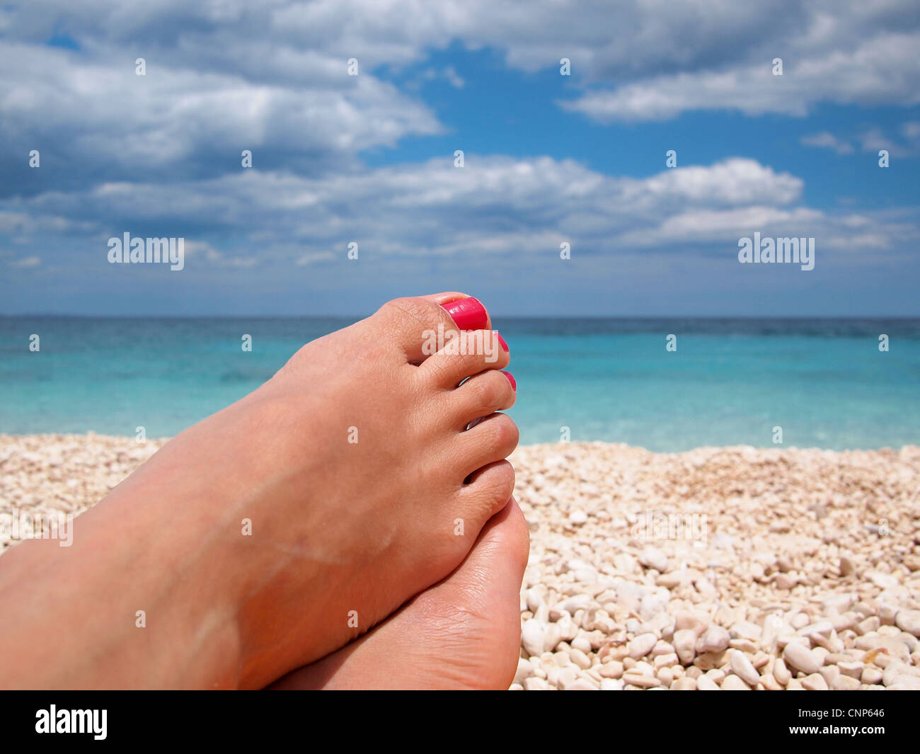 Female feet with red polished nails relaxing lazy on the beach. - Stock Image