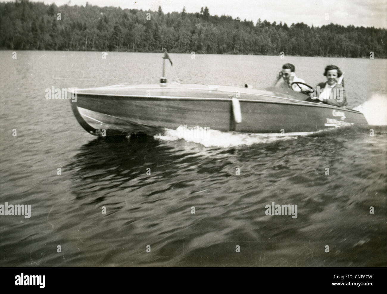 Circa 1940s photograph of a man and woman riding a motorboat on a lake, USA. - Stock Image