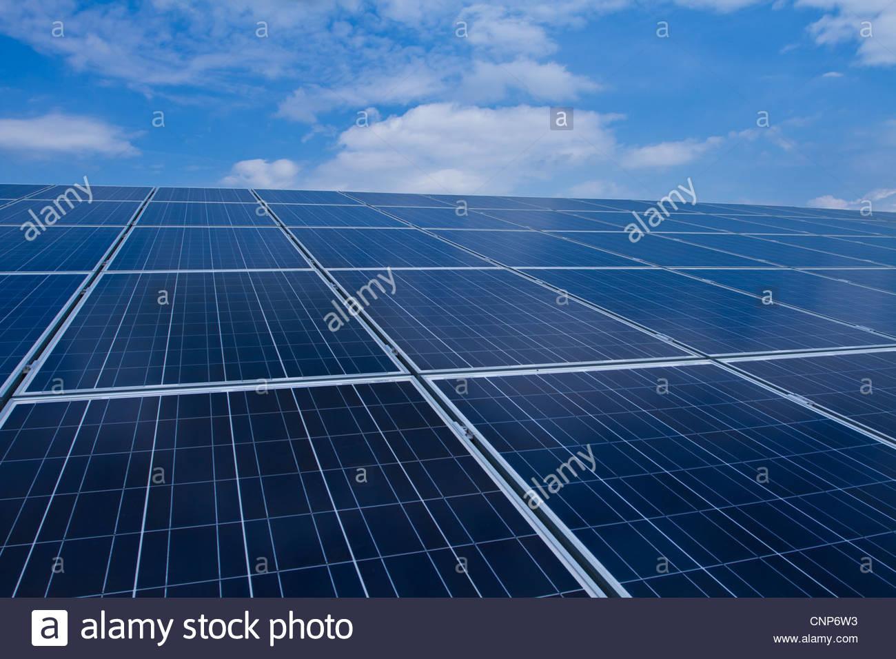 Solar panels under blue sky - Stock Image