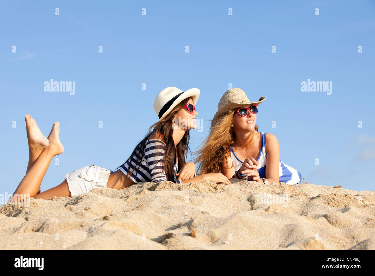 girls laying in sand on summer vacation Stock Photo