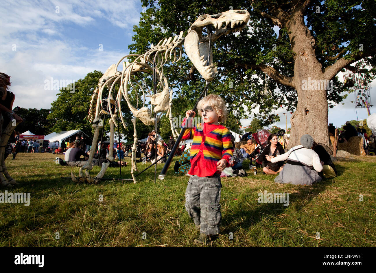 Child playing with a life size replica of a dinosaur skeleton at Playgroup Festival in Kent. Stock Photo