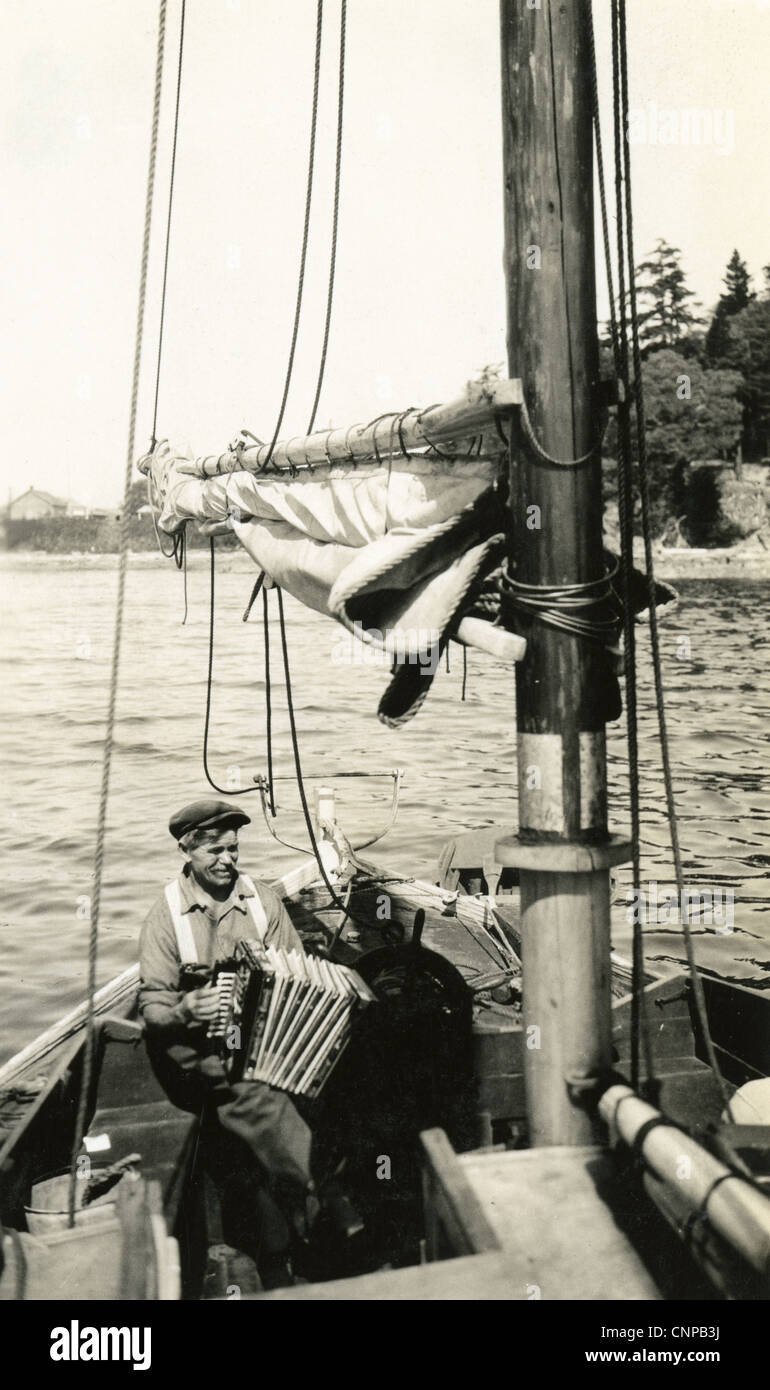 Circa 1930s photograph, elderly man on a boat with an accordion. - Stock Image