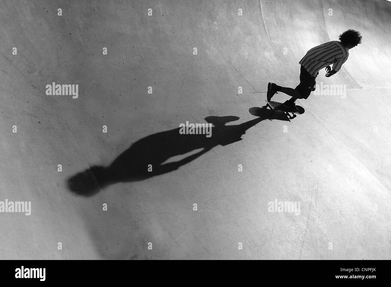 Skateboarder skating the bowl, - Stock Image