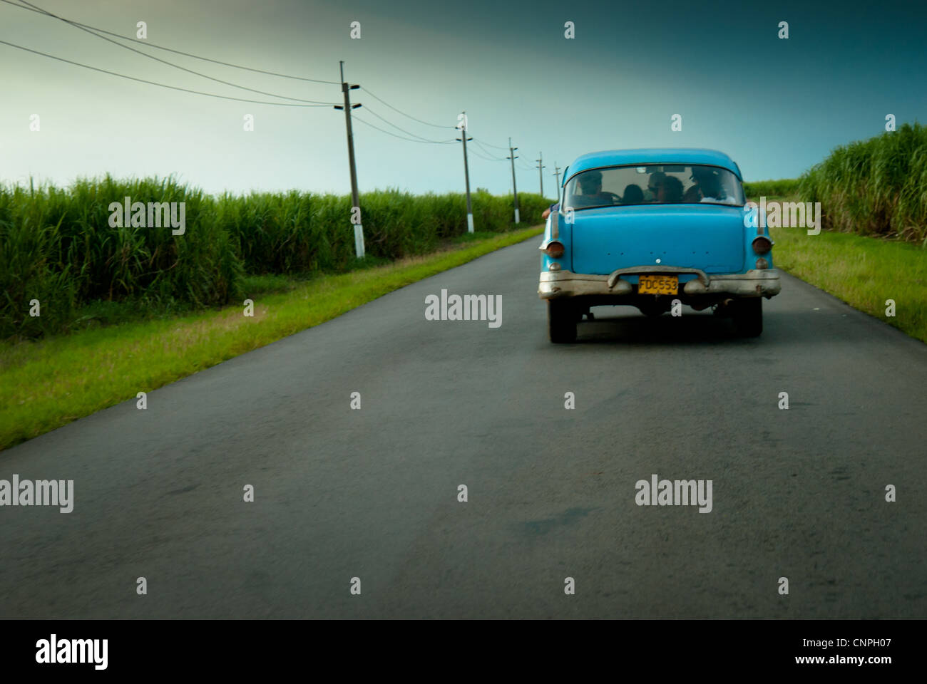 an old american car driving away fully loaded with people stock
