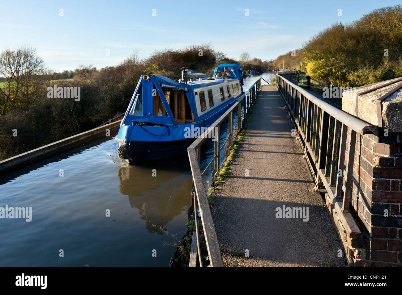 A canal boat crosses the Cosgrove Iron Trunk Aqueduct on the Grand Union Canal near to Milton Keynes, UK - Stock Image