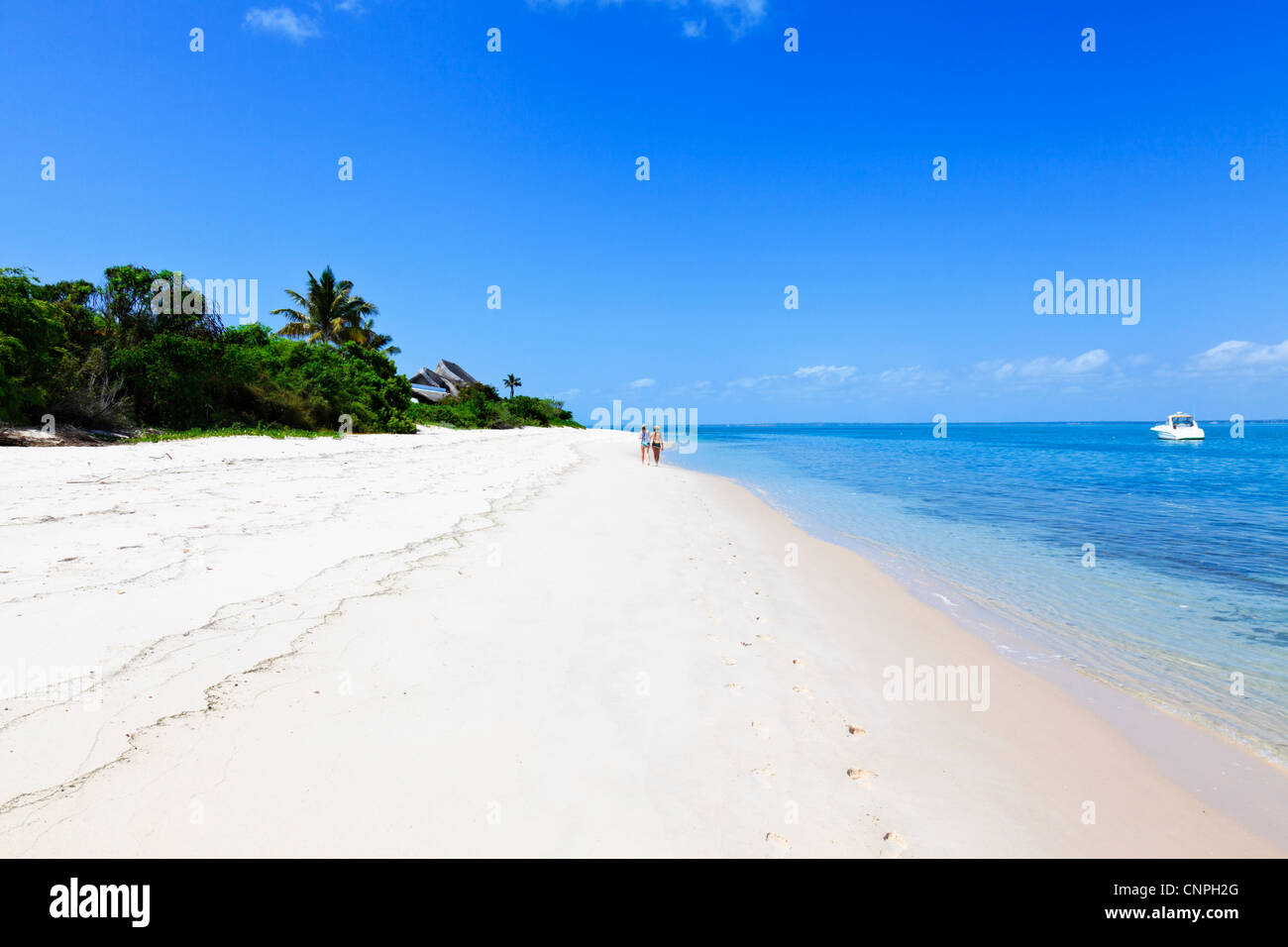 Women walking on island beach in the Mozambique archipelago. - Stock Image