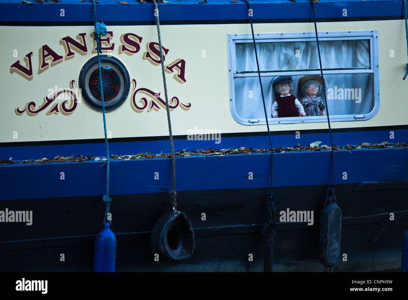 Two dolls stare out of a canal boat window on the Grand Union Canal near to Milton Keynes, UK. - Stock Image