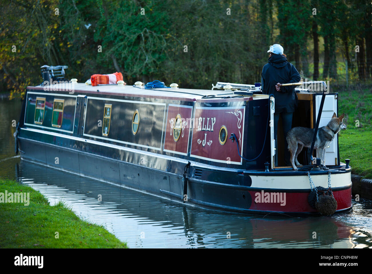 A canal boat under way on the Grand Union Canal near to Milton Keynes, UK. - Stock Image