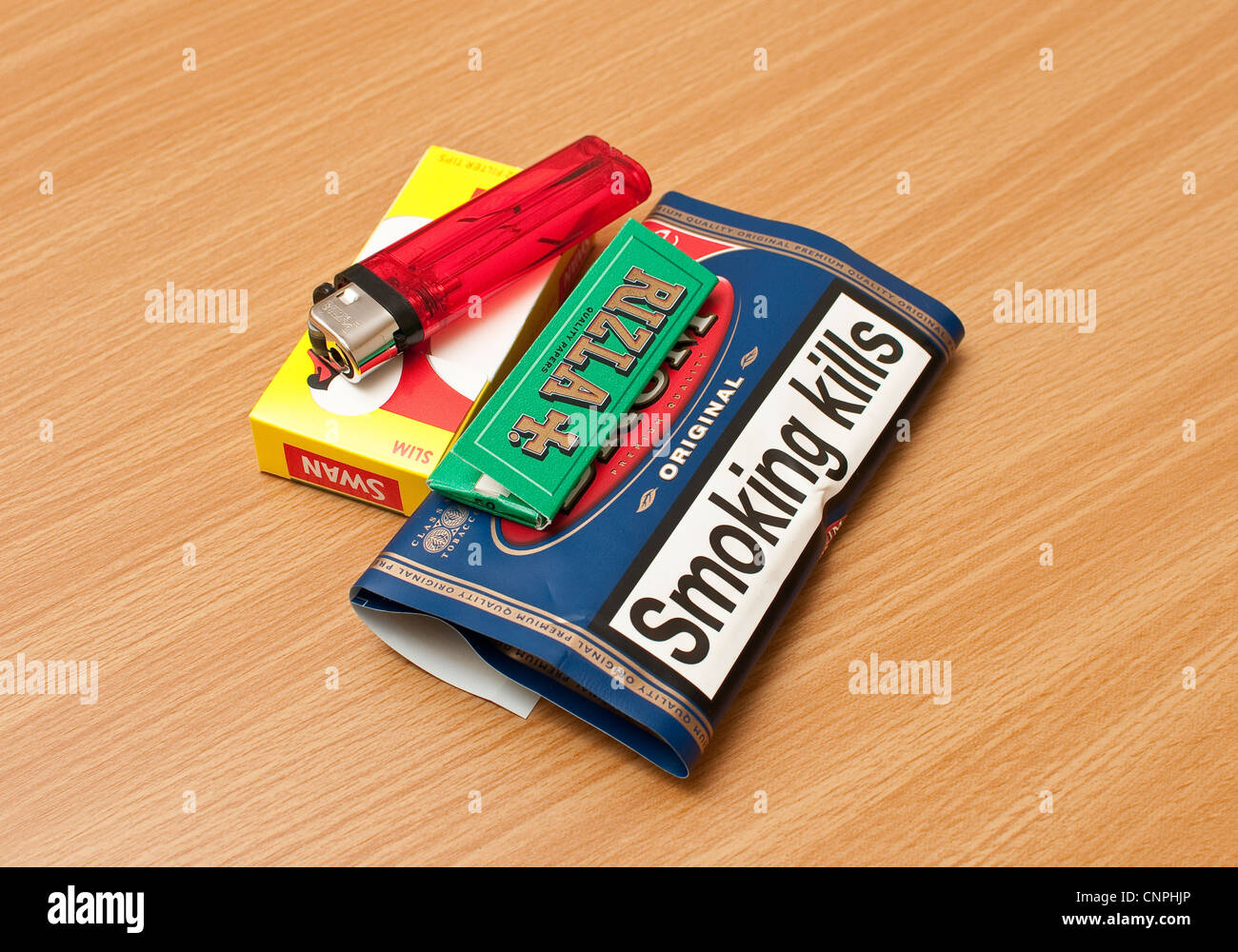 Rolling tobacco green rizla filters and lighter - Stock Image