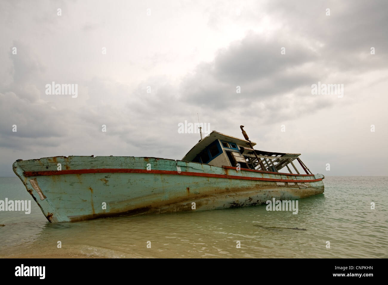 Rusty and forgotten boat on a shore - Stock Image