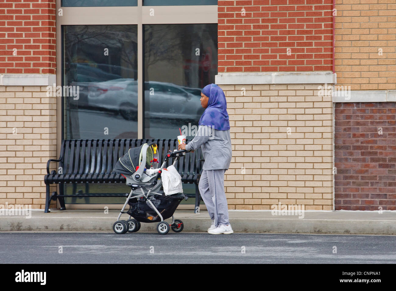 A black woman walking a baby in shopping center wearing traditional garb - Stock Image