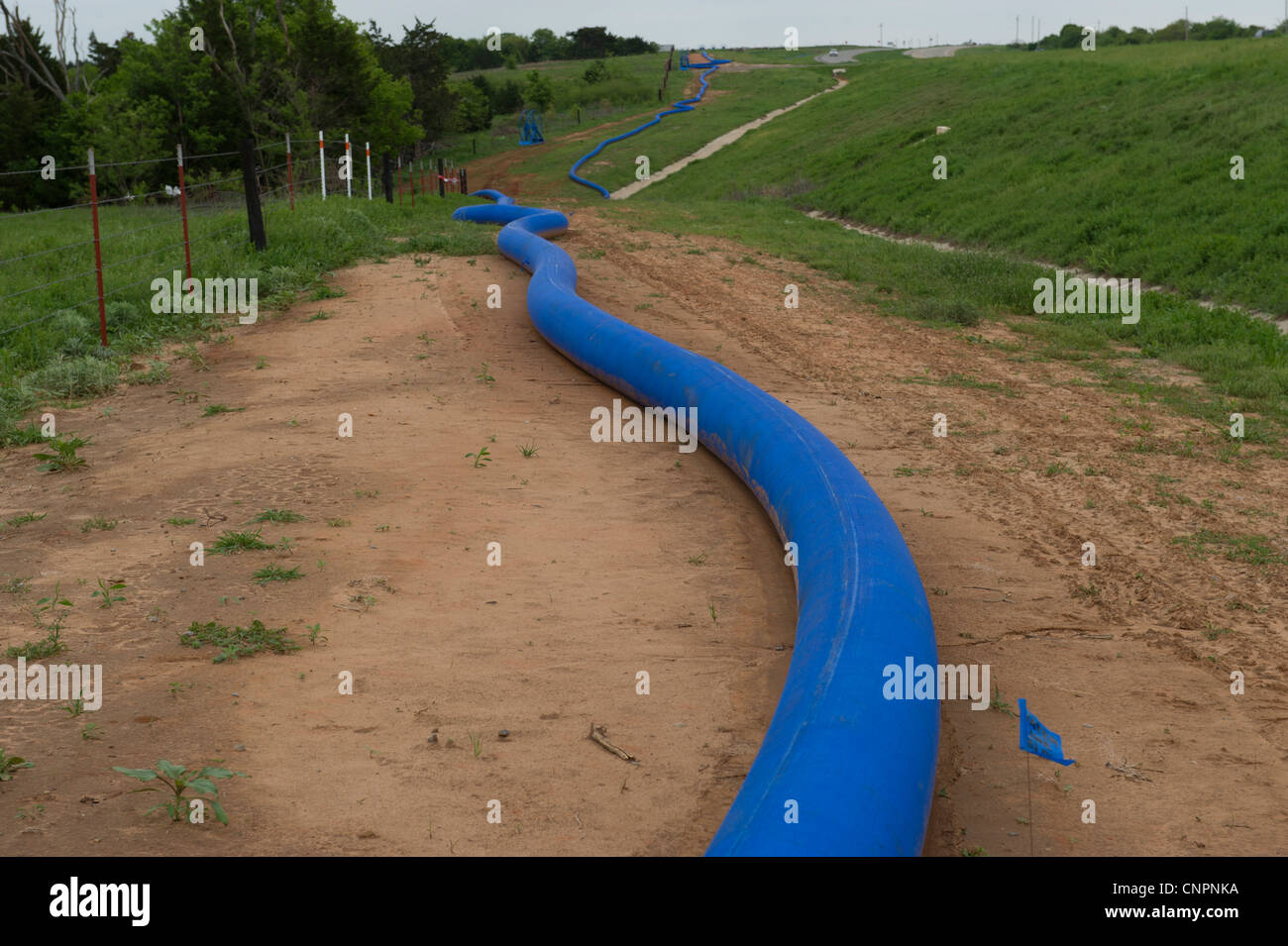 A large hose used to pump water to a natural gas well fracking site from a local lake - Stock Image