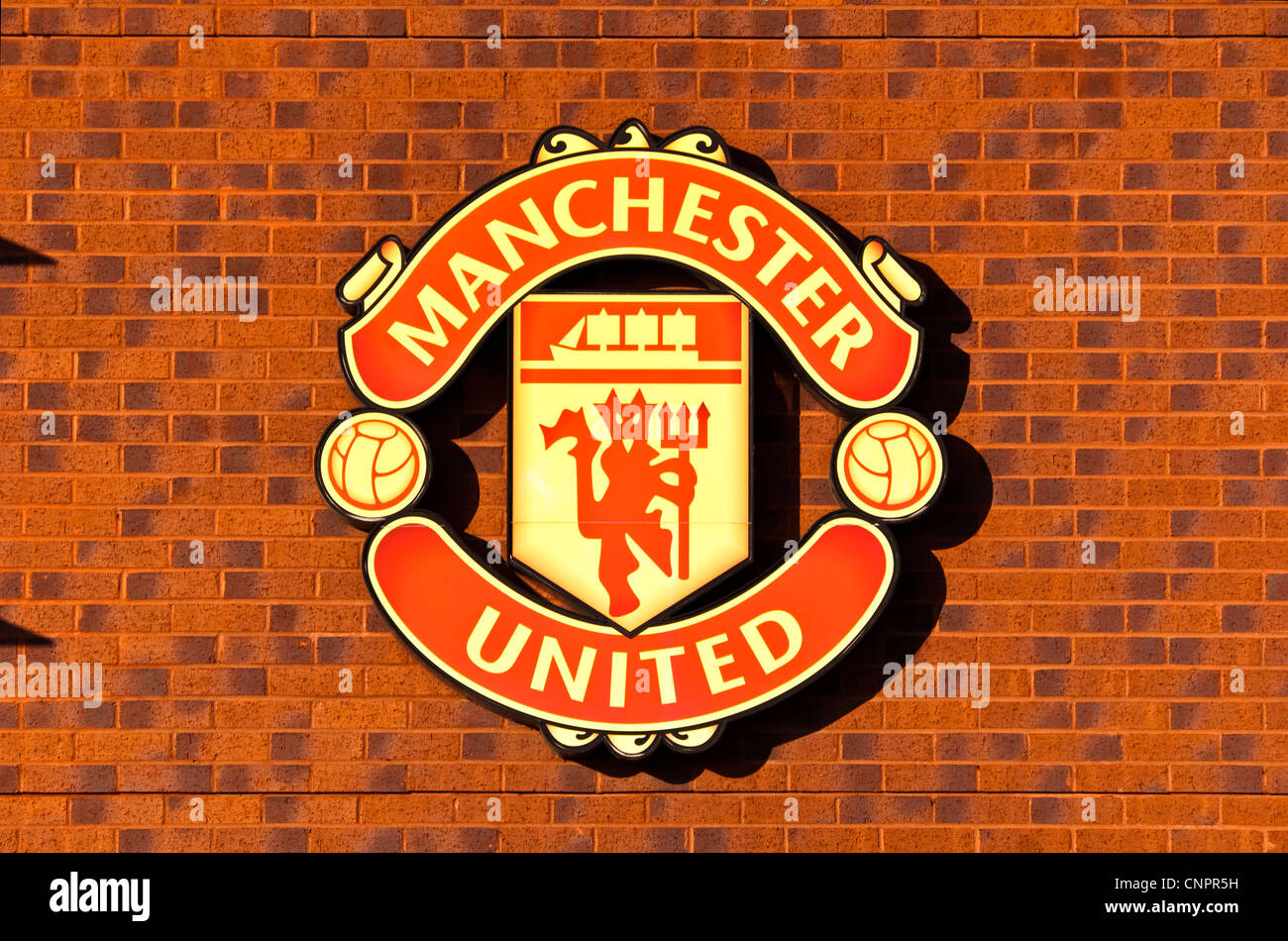 Manchester United emblem on the wall outside the United store, Old Trafford, Manchester, England, UK - Stock Image