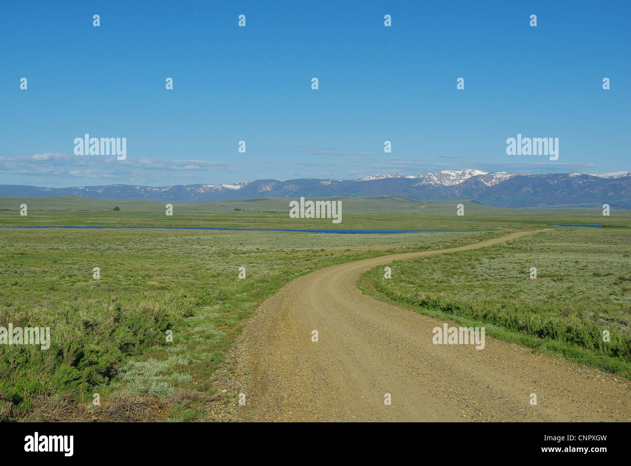 Dirt road through blue lakes to Rockies, Arapaho National Wildlife Refuge, Colorado - Stock Image