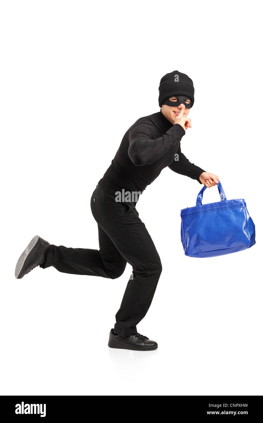 Full length portrait of a thief running with a stolen purse and finger on lips gesturing silence isolated on white - Stock Image