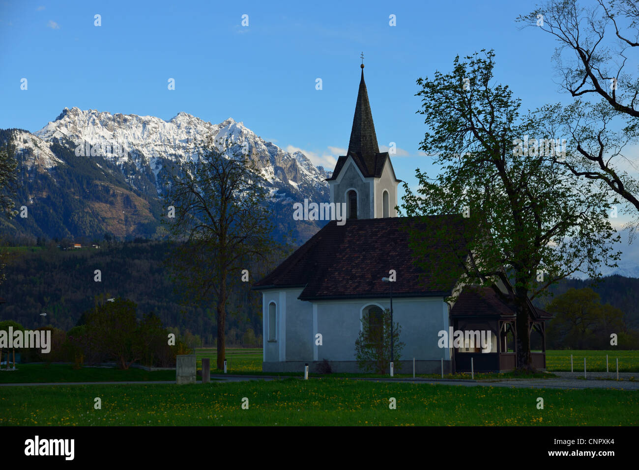 The country church of Bangs (Austria) against the three sisters mountain in Liechtenstein, FL Stock Photo