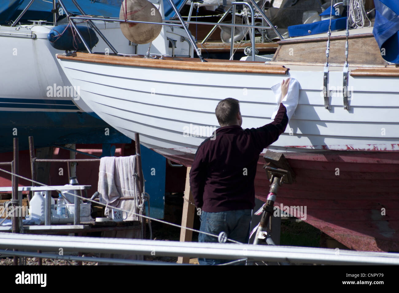 Man cleaning sailing boat in boatyard - Stock Image