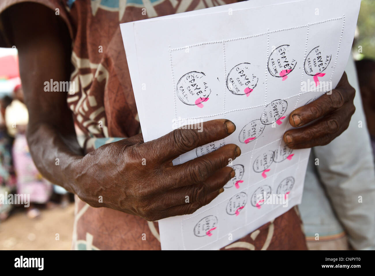 A woman holds a sheet of coupons she's received during a non-food item fair at the Miketo IDP settlement, Katanga - Stock Image