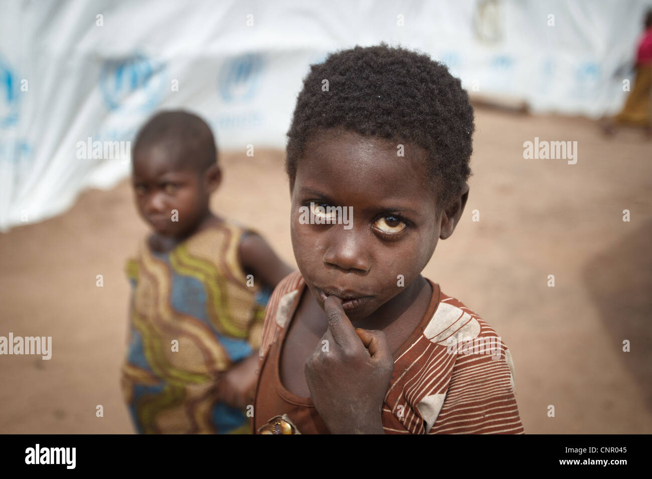 Children stand between basic shelters made of tarp at the Miketo IDP settlement, Katanga province, Democratic Republic - Stock Image