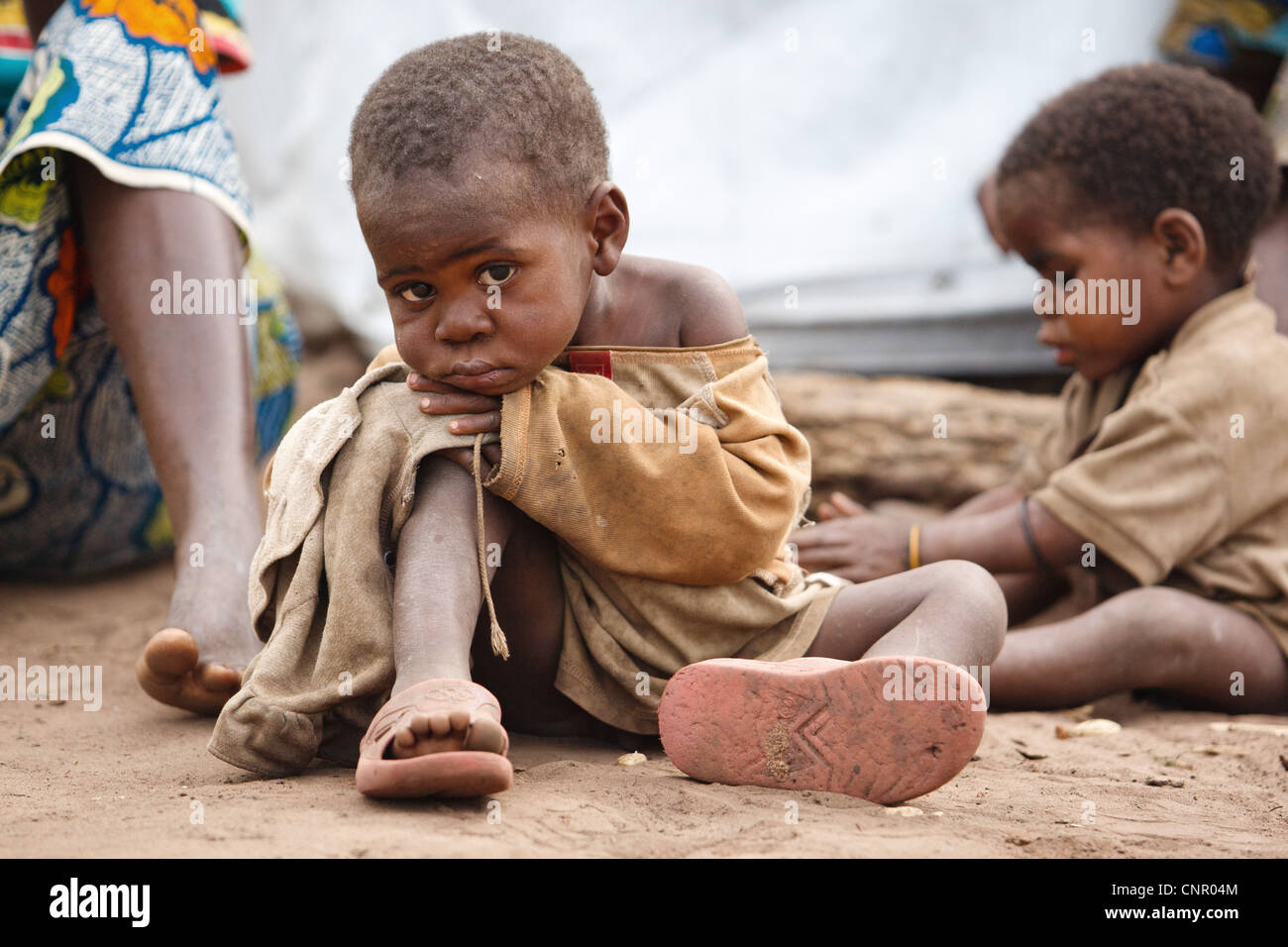 A child sits on the ground at the Miketo IDP settlement, Katanga province, Democratic Republic of Congo - Stock Image