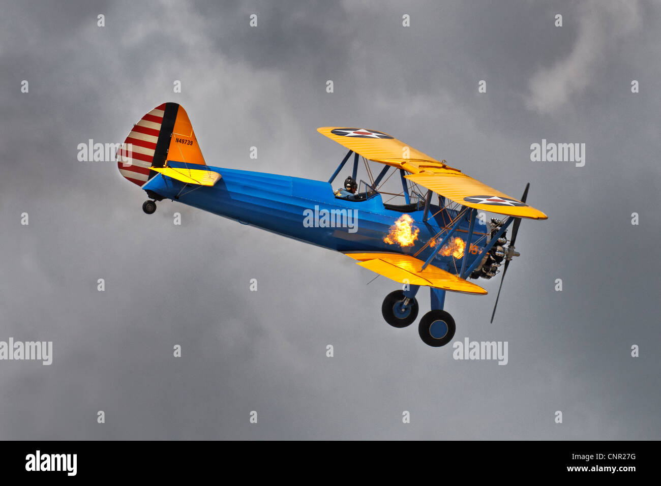 Boeing PT17 Stearman bi-plane American training aircraft with flames coming from the engine exhaust pots Stock Photo