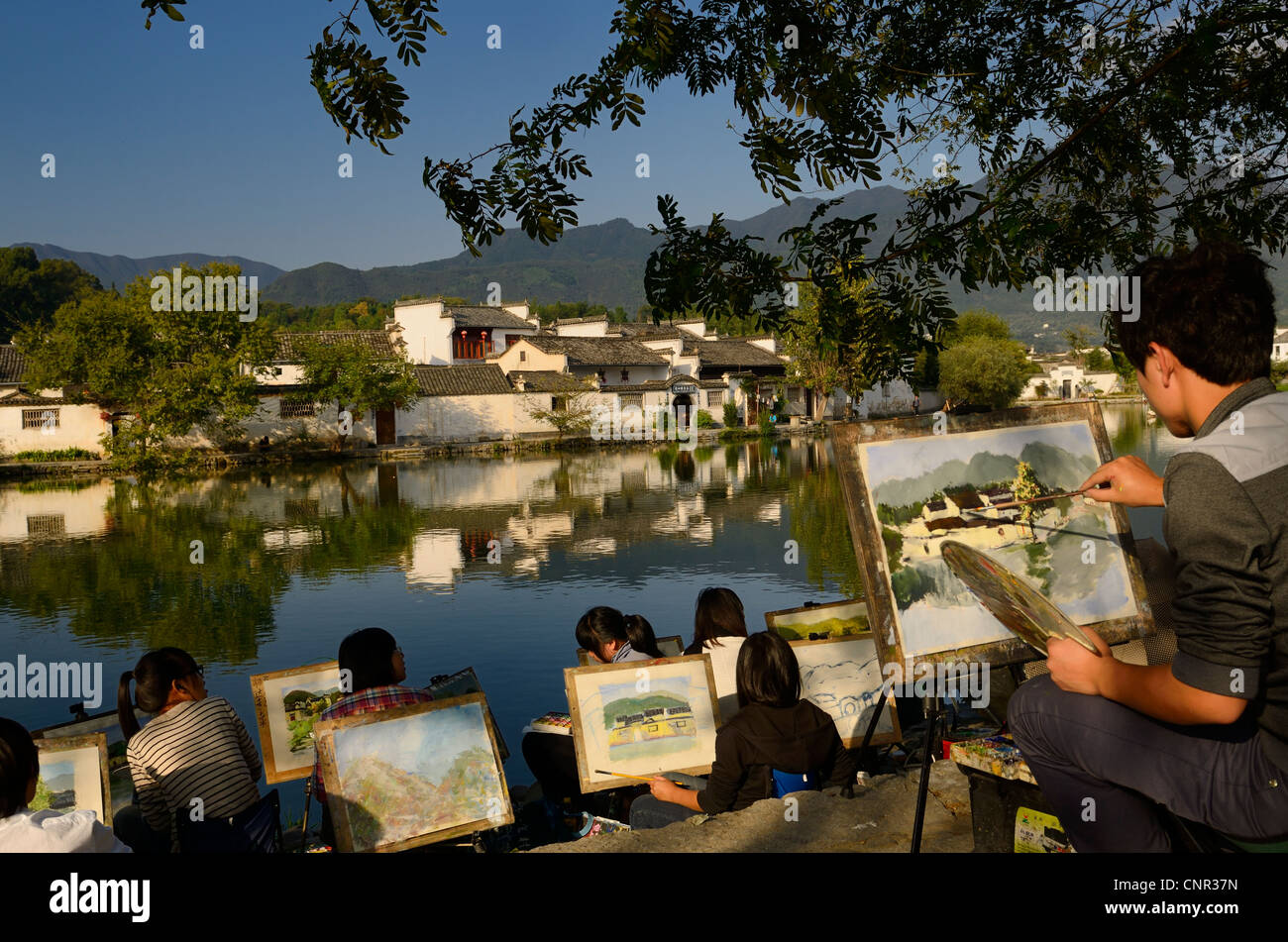 Group of student artists painting South Lake in Hongcun World Heritage Site Anhui Province Peoples Republic of China - Stock Image
