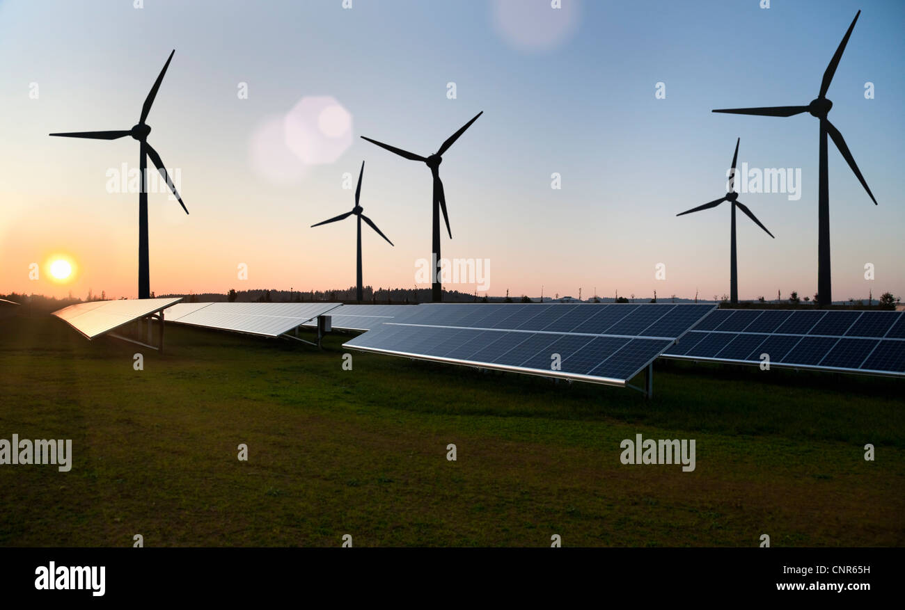 Wind turbines and solar panels in field - Stock Image