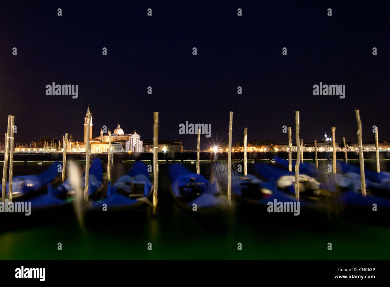 Gondolas anchored on Grand Canal in Venice - long exposure night shot with motion blurred gondolas (color toned - Stock Image