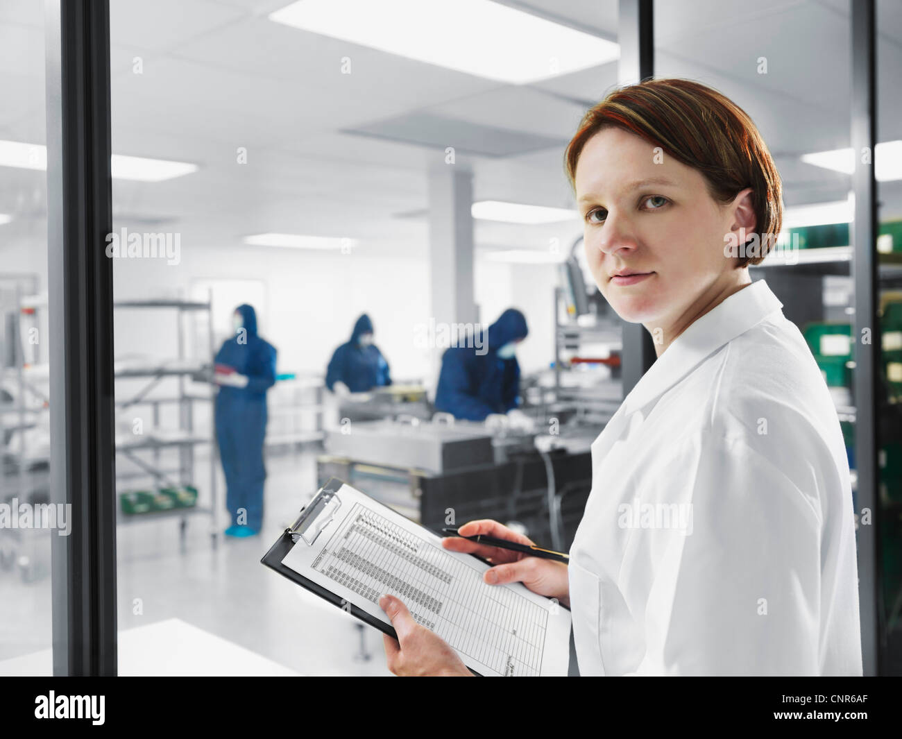 Scientist using clipboard in lab Stock Photo