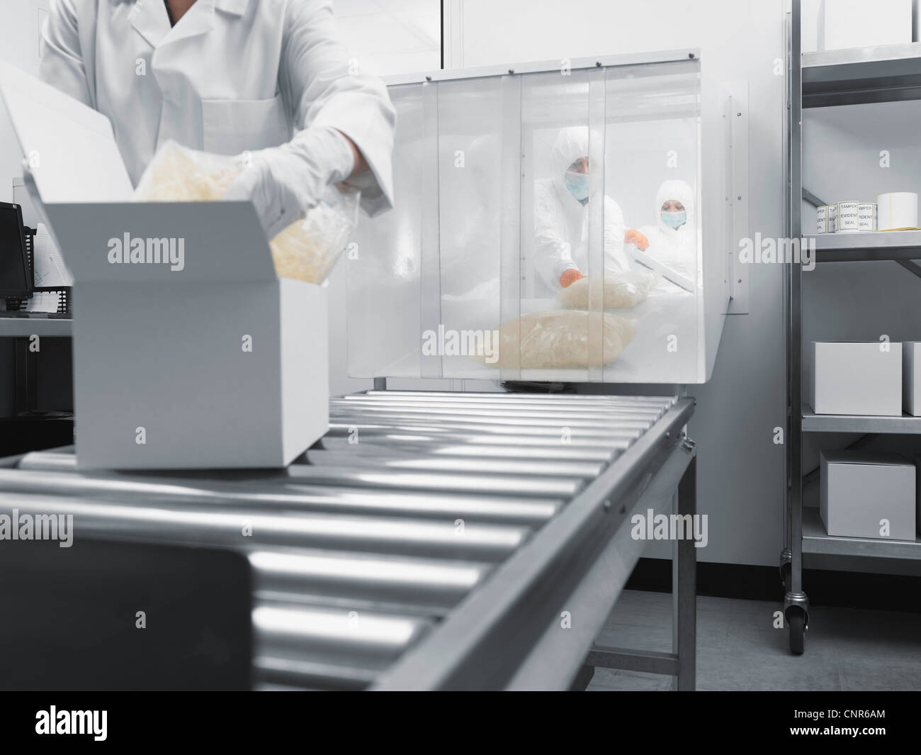 Scientist working on assembly line Stock Photo